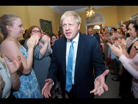 Britain's new Prime Minister Boris Johnson is welcomed into 10 Downing Street by staff in London, on Wednesday, July 24.