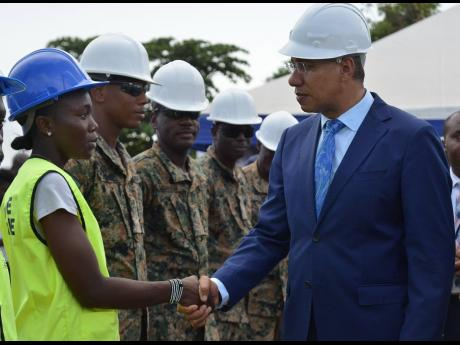 Prime Minister Andrew Michael Holness greets Mashekia McKenzie, a trainee with the Housing, Opportunity, Production and Employment (HOPE) programme, during a tour of the new police station on Olympic Way, a site where unattached youth are trained under the HOPE  programme.