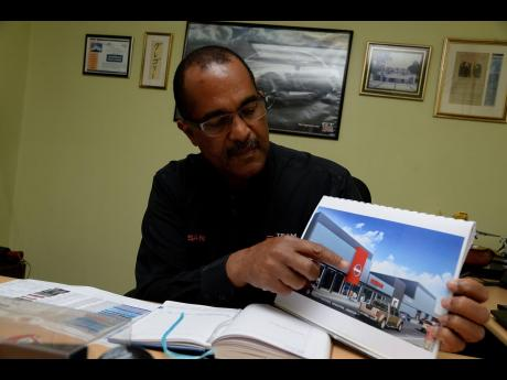 In this January 30, 2018 file photo, Managing Director of Fidelty Motors Limited Major Gregory Webster displays an image of the Nissan showroom to be developed in downtown Kingston.