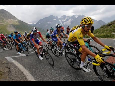 France's Julian Alaphilippe, wearing the overall leader's yellow jersey, climbs the Galibier pass during the 18th stage of the Tour de France cycling race over 208 kilometres, with the start in Embrun and the finish in Valloire, France, yesterday.