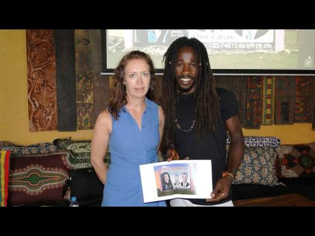 United Kingston mural specialist Tracey Thorne (left) with one of the Jamaican artists, Katapul, whose works she has photographed for her documentary photography project called 'Hand-painted Jamaica'.