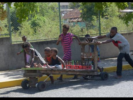 Rushane Smith was photographed pushing this handcart with these children and crates of bottles along Duke Street in Kingston on the morning of Wednesday, January 4, 2017.