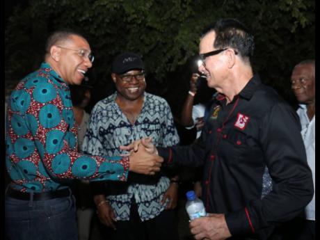 Prime Minister Andrew Holness (left) and Joe Bogdanovich greet each other at Reggae Sumfest as Minister of Tourism Edmund Bartlett looks on.