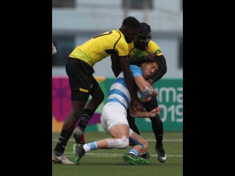Franco Sabato (centre), of Argentina, is tackled by Mikel Facey (left), and Oshane Edie, of Jamaica, during their Rugby Sevens match at the Pan American Games in Lima, Peru, yesterday. Argentina won the match 52-0.