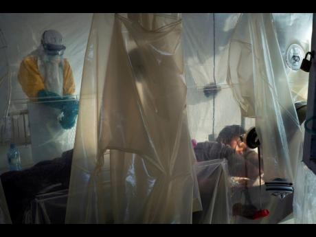 In this Saturday, July 13, 2019 photo, health workers wearing protective gear check on a patient isolated in a plastic cube at an Ebola treatment centre in Beni, Congo.