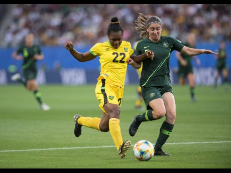 Mireya Grey (left) of the Reggae Girlz goes on the attack under pressure from Australia's Karly Roestbakken in the Jamaica vs Australia fixture of the FIFA Women's World Cup 2019 at Stade des Alpes in Grenoble, France, on Tuesday, June 18, 2019.