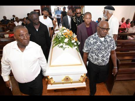 Pall-bearers carry the casket at the thanksgiving service for late Gleaner journalist Marc Stamp at the Dovecot Chapel, Dovecot Memorial Park, in Spanish Town, St Catherine, yesterday.