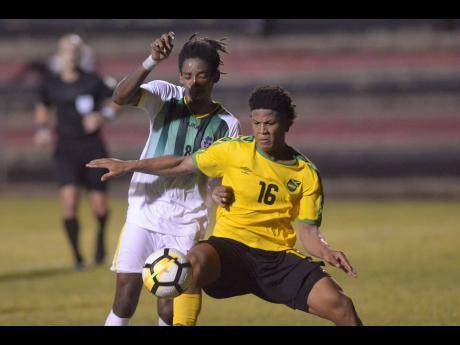 Jamaica's Nicque Daley (right) shields the ball from Dominican defender Jolly Fitz during their Olympic Games qualifier at the Anthony Spaulding Sports Complex in Kingston, Jamaica, on Wednesday, July 17. The game ended 1-1.