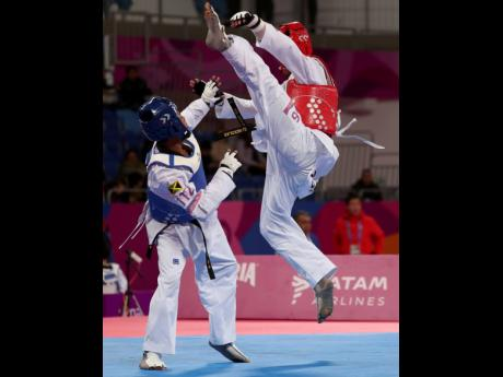 Brandon Austin of Jamaica (left) competes against Carl Nickolas Jr of the United States during a men's under-68kg Taekwondo round-of-eight fight at the Pan American Games in Lima, Peru, yesterday.