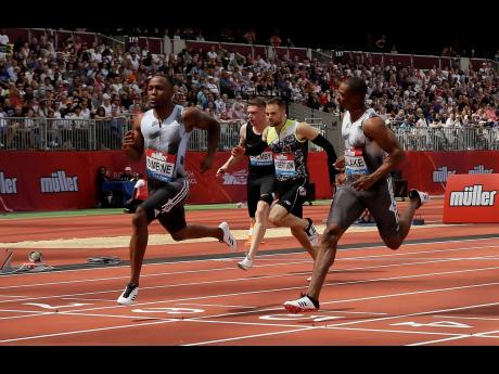 Akani Simbine (left) of South Africa crosses the finish line ahead of Yohan Blake (right) of Jamaica to win a men's 100m heat at the IAAF Diamond League meet at London Stadium in London, England, on Saturday, July 20.