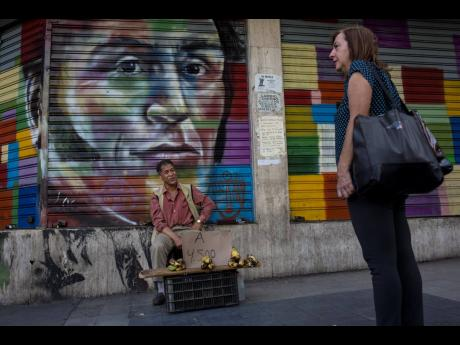 A street vendor sells bananas in front of a painting with the image of Venezuelan Independence hero Simón Bolívar, in Caracas, Venezuela,  on Tuesday, July 16.