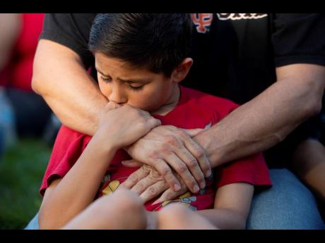 Robbie Ramirez, 10, holds on to his father, Robert Ramirez, during a vigil for victims of a Sunday evening shooting that left three people dead at the Gilroy Garlic Festival on Monday, July 29, in Gilroy, California.