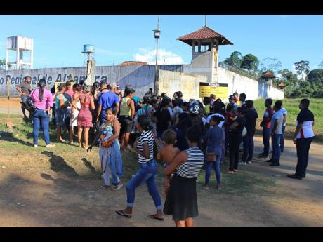 People seek information about family members who are prisoners after a riot inside the Regional Recovery Center in Altamira, Brazil, on Monday. At least 57 prisoners were killed by other inmates during clashes between organised crime groups in the Altamira prison in northern Brazil on Monday, with 16 of the victims being decapitated, according to prison officials.