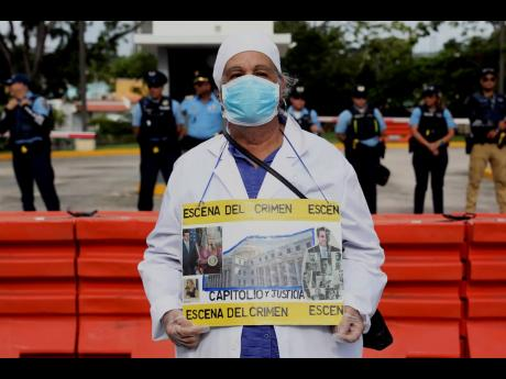 A man dressed as a doctor holds a sign that reads, 'Crime scene' in Spanish during a protest at the Department of Justice to demand the resignation of Justice Secretary Wanda Vázquez in San Juan, Puerto Rico, on Monday, July 29, 20.