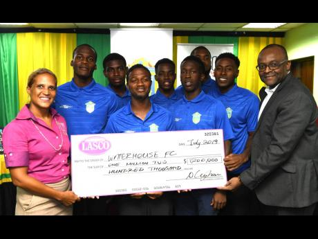 Danielle Cunningham (left), beverage marketing manager, LASCO Distributors, presents a cheque for $1.2 million to Donovan White (right), president of the Waterhouse Football Club, at yesterday's media briefing ahead of the Scotiabank Concacaf League match between Waterhouse and HS Herediano of Costa Rica. Sharing in the moment are Waterhouse head coach Marcel Gayle (fourth left) and several players of the club. The briefing was held at the offices of the Jamaica Football Federation.