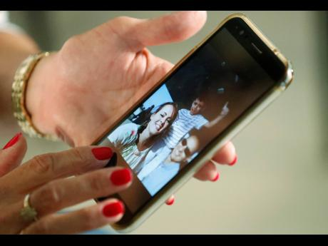 In this June 20, 2019 photo, Mary Sardinas, 60, shows a photo of her son, daughter-in-law and grandson in Cuba as she speaks during an interview with The Associated Press in Miami. Sardinas is among thousands of Cubans living in the United States whose hopes of reuniting with family members have been put on hold since September 2017, when the Trump administration pulled most of its embassy staff out of Cuba in response to a mysterious illness that struck at least two dozen diplomats or their relatives.