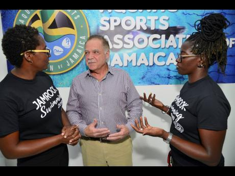Martin Lyn (centre), president of the Aquatic Swimming Association of Jamaica, chats with Sophia Whyte-Givans (left), team manager, and Gillian Millwood, head coach of Jamaica's Swim Team to the 25th staging of the Goodwill Games, which will be held in Suriname between August 16 and 18. The press conference was held at the National Aquatic Centre, Independence Park, in Kingston on Tuesday.