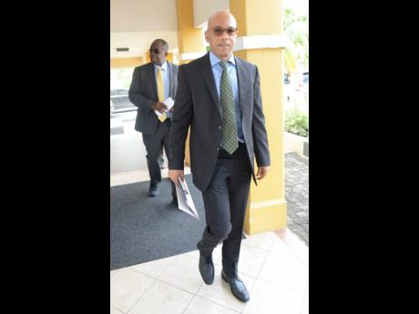 NCB Financial Group President and CEO Patrick Hylton walks behind his deputy and chief financial officer, Dennis Cohen, on arrival at an investors' briefing held in September 2017.