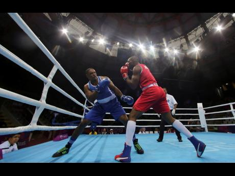 Cristian Salcedo of Colombia (right) throws a punch to Ricardo Brown of Jamaica during the second round of their men's heavyweight 91+kg  semi-final boxing match at the Pan American Games in Lima, Peru, yesterday.