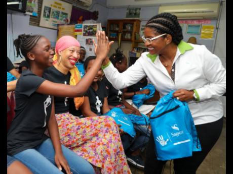 Sagicor Life Financial Adviser Candies Campbell (right) gives Kayci Grant, 13-year-old Bishop Gibson High School student, a high five during the financial management session at the inaugural The Walk Camp in Jamaica, put on by International Jamaica-born supermodel, Stacey McKenzie (left). The Walk Camp was a daily camp held at the Half-Way Tree Primary School for two weeks.