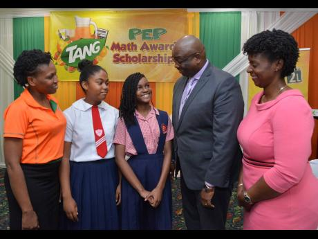 Gabrielle Nelson (second left) and Zoe Hume (centre) talk with Dr Garth Anderson, president of the Jamaica Teachers' Association, and Dr Tamika Benjamin, national mathematics coordinator (right), as Shellian Thompson, brand manager at Tang, looks on during the Tang PEP awards ceremony at The Knutsford Court Hotel on Tuesday.
