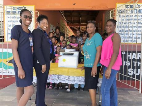 The teaching team and students at the Beersheba Primary School in St Elizabeth were all smiles as they received a donation of a printer valued at J$140,000 from NCB Foundation. The gift is expected to improve the learning environment for the school as they head into exam preparation mode in the next school term. From left are: Donique Bucknor, NCB Black River lobby officer; Mary Singh, NCB Black River service quality manager; Principal Michelle Sanderson and Cara Stone Martin, teacher .
