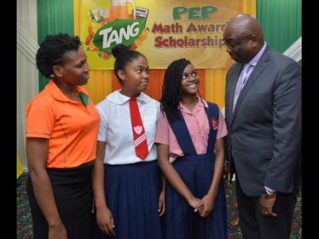 Gabrielle Nelson (second left) and Zoe Hume (second right ) talk with Dr Garth Anderson (right), president of the Jamaica Teachers' Association, and Shellian Thompson, brand manager at TANG, during the Tang PEP awards ceremony held at the Knutsford Court Hotel on Tuesday.