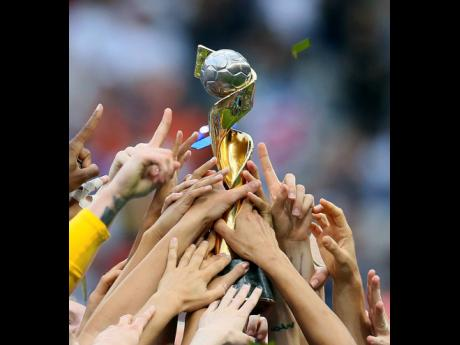 USA players hold the trophy as they celebrate their victory in the FIFA Women's World Cup final in Decines, outside Lyon, France,  on Sunday, July 7.
