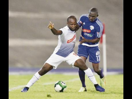Javon East (left), representing Portmore United, keeps Xavian Virgo of Mount Pleasant away from the ball in the Red Stripe Premier League semi-final at the The National Stadium on Monday, April 15.