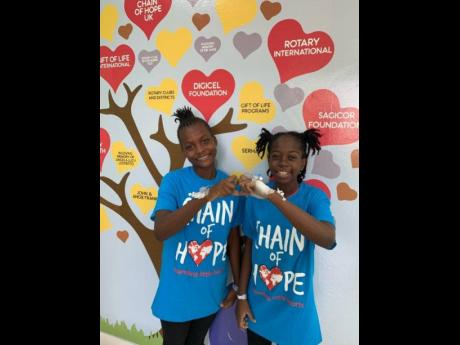 Abigail (left) from Tivoli Gardens and Deanna from Duhaney Park celebrate their successful cardiac catheterisation procedures, which were done in the recently commissioned Biplane Cardiac Catheterisation Lab at the Paediatric Cardiac Centre, Bustamante Hospital for Children, during a recent Chain of Hope medical mission.