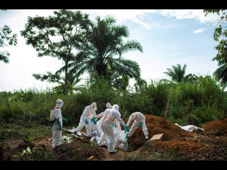 In this Sunday, July 14, photo, workers bury the remains of Mussa Kathembo, an Islamic scholar who had prayed over those who were sick in Beni, Congo. Kathembo died of Ebola.