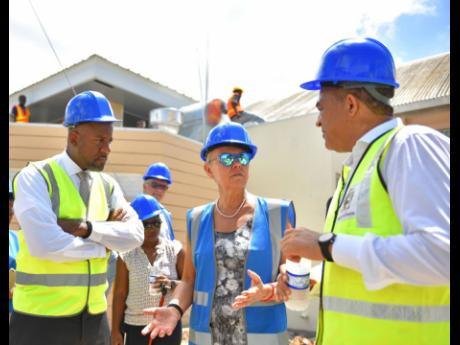 Minister of Health and Wellness Dr Christopher Tufton (right) and director general, Planning Institute of Jamaica, Dr Wayne Henry (left), listen to Head of the European Union Delegation to Jamaica, Malgorzata Wasilewska, during a tour of the construction site for a high dependency unit at the Spanish Town Hospital in St Catherine on Wednesday.