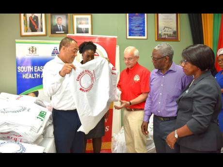 Minister of Health and Wellness Dr Christopher Tufton (left) looks at a sheet, which was among 580 pieces of bed linen donated by the Chinese Benevolent Association (CBA) to the Kingston Public Hospital (KPH), at the hospital's downtown Kingston location on Wednesday. From second left are: Senior Medical Officer, KPH, Dr Natalie Whylie; President, CBA, Robert Hew; Chairman, South East Regional Health Authority, Wentworth Charles, and Chief Executive Officer, KPH, Colleen Wright.