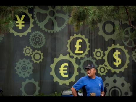 In this July 20, 2018, file photo, a deliveryman for American based pizza chain Domino's prepares to make a delivery near a mural displaying Chinese yuan and other world currency symbols on the outside of a bank in Beijing.