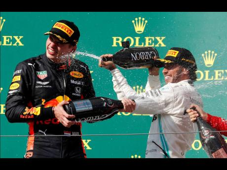 Mercedes driver Lewis Hamilton (right), winner of the Hungarian Formula One Grand Prix, celebrates on the podium with second placed Red Bull driver Max Verstappen, at the Hungaroring racetrack in Mogyorod, northeast of Budapest yesterday. Ferrari's Sebastien Vettel finished third.