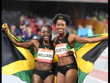 Jamaican duo Kimberly Williams (left) and Shaneika Ricketts pose with the flag after mining gold and silver in the triple jump event at the 2018 Commonwealth Games in Gold Coast, Australia.