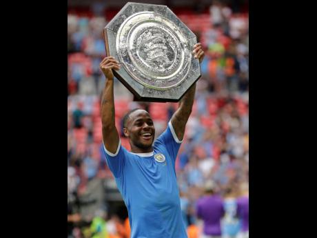Jamaica-born Manchester City goalscorer Raheem Sterling lifts the trophy after the English Community Shield match between Liverpool and Manchester City at Wembley Stadium in London, yesterday. City won 5-4 on penalties after a 1-1 regulation time scoreline.