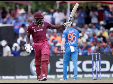 West Indies' Rovman Powell raises his bat after scoring 50 runs during the second Twenty20 international cricket match against India yesterday in Lauderhill, Florida.