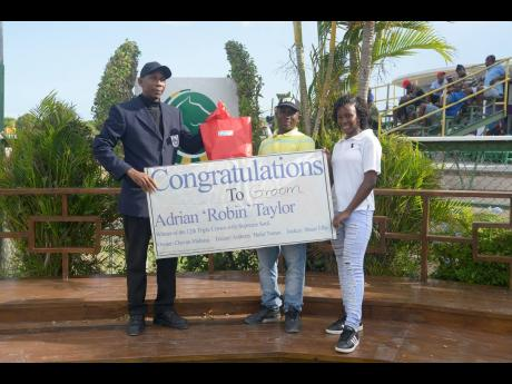 Clive 'Freezing Rain' Evans, (left) 2017 Hall of Famer, makes a special presentation to groom Adrian 'Robin' Taylor (centre) and his daughter, Tarika Taylor, at Caymanas Park on Saturday, August 3, 2019.