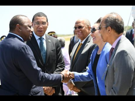 Kenyan President Uhuru Kenyatta greets Foreign Affairs Minister Kamina Johnson Smith following his arrival at the Norman Manley International Airport yesterday. Prime Minister Andrew Holness (second left), Opposition Leader Dr Peter Phillips (third left) and Dr Horace Chang (right) look on. Kenyatta is on a three-day state visit to the island.