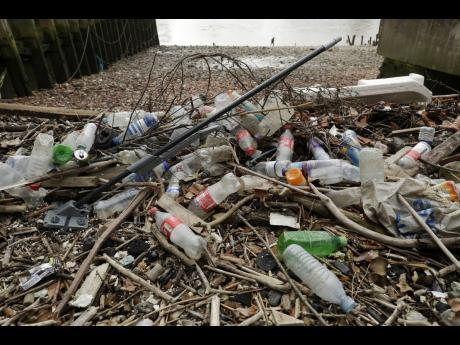 In this February 5, 2018 file, photo, plastic bottles and other plastics, including a mop, lie washed up on the north bank of the River Thames in London. European Union officials agreed on Wednesday, December 19, 2018, to ban some single-use plastics such as disposable cutlery, plates, and straws in an effort to cut marine pollution. The measure will also affect plastic cotton buds, drink stirrers, balloon sticks, and single-use plastic and polystyrene food and beverage containers.
