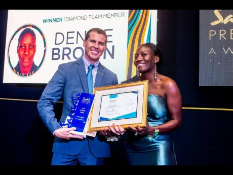 SRI Winner: Denise Brown, Sandals Resorts International's Diamond Team Member of the Year and the company's group shipping clerk, is presented with the winning trophy and prizes by the company's Deputy Chairman, Adam Stewart, at the recently held Annual Prestige Awards Ceremony.
