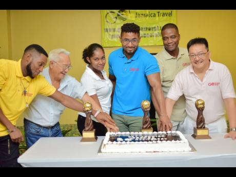 From left: The GoJamaica Travel team Dreon Harrison, Michael Chin Tung, Shandice Cammock, Bryan Clayton, Robert Ferguson, and Dave Chin Tung cut their 20th-anniversary cake recently at The Knutsford Court Hotel in Kingston.
