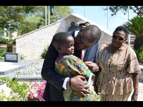 Uhuru Kenyatta, president of the Republic of Kenya, chats with Chavon Brown as Culture Minister Olivia Grange looks on at the floral tribute at shrine of National Hero Marcus Garvey at National Heroes Park in Kingston yesterday.