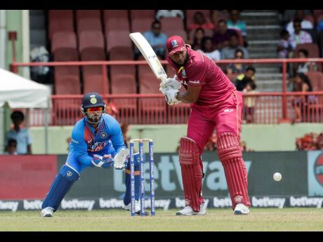 West Indies batsman Kieron Pollard (right) makes a shot as India wicket-keeper Rishabh Pant looks on during their third T20 international cricket match in Providence, Guyana, yesterday. Pollard struck 58 runs as the Windies lost by seven wickets.