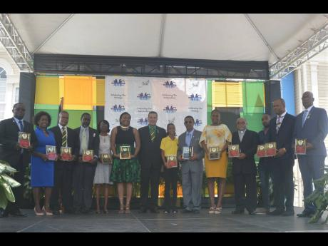 Montego Bay Mayor Homer Davis (centre) poses with the 13 recipients of the St James Municipal Corporation's Spirit of Independence Awards and the Mayor's Special Awards at a civic ceremony in Sam Sharpe Square, Montego Bay, yesterday.