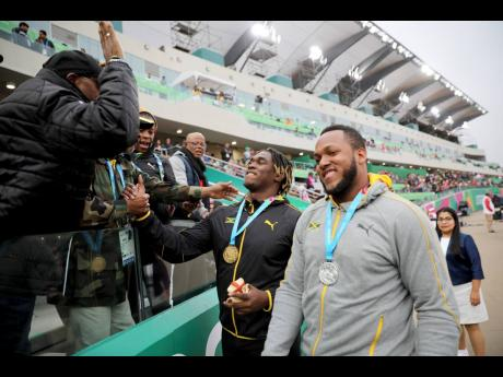 Jamaica's Fedrick Dacres is greeted by coaches and fans after receiving his gold medal for the men's discus throw competition during the Pan American Games in Lima, Peru, Tuesday, August 6, 2019. At right is friend and silver medallist Traves Smikle, also of Jamaica.