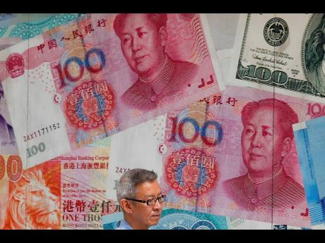 In this Tuesday, August 6, 2019, photo, a man walks by a money exchange shop decorated with Chinese yuan banknotes and other countries currency banknotes at Central, a business district in Hong Kong.