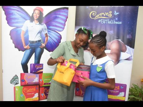 LASCO Curves Primary Exit Profile (PEP) Scholarship recipients Ashiekie Hamilton (left) of St Peter Claver Primary and Merisha Miller of St Catherine Primary explore their gift packages, courtesy of LASCO Curves, during a special ceremony to honour the students' outstanding academic achievements on Tuesday, July 30, at LASCO Distributors Limited in White Marl, St Catherine. The top performers will attend Campion College in the new school year.