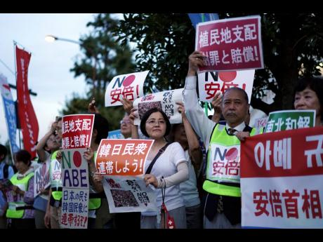 AP  A group of protesters gather outside Japanese Prime Minister Shinzo Abe's residence in Tokyo Thursday, August 8. They staged a rally with placards to urge the government to apologize for wartime atrocities in an effort fix rapidly souring relations.